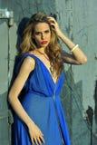 Fashion model posing sexy, wearing long blue evening dress Stock Photo