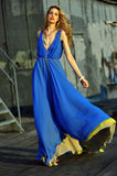 Fashion model posing sexy, wearing long blue evening dress Royalty Free Stock Photo