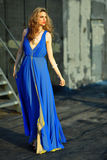 Fashion model posing sexy, wearing long blue evening dress