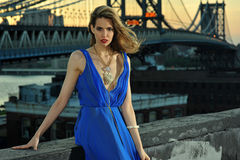 Fashion model posing sexy, wearing long blue evening dress on rooftop location Royalty Free Stock Image