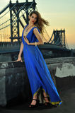 Fashion model posing sexy, wearing long blue evening dress on rooftop location Royalty Free Stock Photography