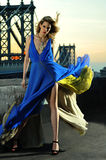 Fashion model posing sexy, wearing long blue evening dress on rooftop location Royalty Free Stock Images