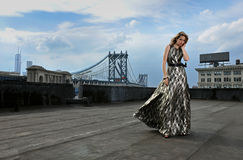 Fashion model posing sexy, wearing long evening dress on rooftop location stock photo