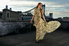 Fashion model posing sexy, wearing long evening dress on rooftop location Royalty Free Stock Photos