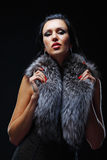 Fashion model posing in studio covering her neck in a fur Royalty Free Stock Images