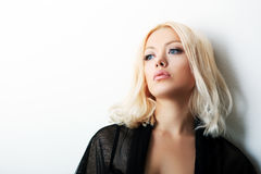 Fashion model posing. In studio. Portrait of a beautiful blond woman with blue eyes Stock Images