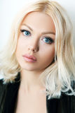 Fashion model posing. In studio. Portrait of a beautiful blond woman with blue eyes Stock Photo