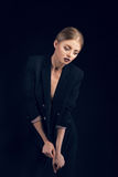 Fashion model posing in suit on black background Royalty Free Stock Photography