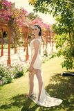 Fashion model posing in white dress with legs. On sunny day in blossoming garden. Summer vacation concept. Bride in white wedding dress royalty free stock photos