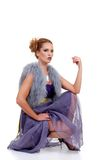 Fashion model with purple dress fur vest. Isolated fashion model with purple dress fur vest sitting on a white background Royalty Free Stock Image