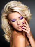 Fashion model with purple manicure and makeup Royalty Free Stock Photography