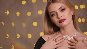 Fashion model puts on necklace in yellow lights bokeh, slow motion. Fashion model puts on necklace in yellow lights bokeh at a studio, luxury expensive jewelry stock footage