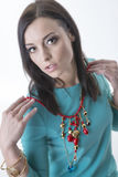 Fashion model putting on necklace Royalty Free Stock Images
