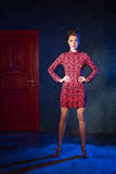 Fashion model in a red dress on a background of the door. Beauti Royalty Free Stock Photo