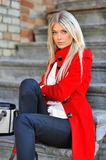 Fashion model in red dress sitting on stairs Stock Images