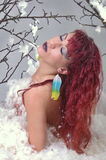 Fashion model with red hair in feathers Stock Image
