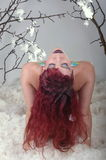 Fashion model with red hair posing in white feathers Royalty Free Stock Photo