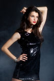 Fashion model in sequin dress. Sexy young woman posing in sequin dress, covered in fog, looking away. Studio image, on black background Stock Photos