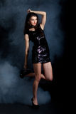 Fashion model in sequin dress. Sexy young woman posing in sequin dress, covered in fog, looking away. Studio image, on black background Stock Image