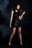 Fashion model in sequin dress. Sexy young woman posing in sequin dress, covered in fog, looking away. Studio image, on black background Stock Photo
