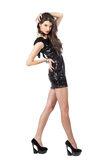 Fashion model in sequin dress. Attractive young woman posing in sequin dress, looking at camera. Studio image, isolated on white background Royalty Free Stock Photo