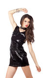 Fashion model in sequin dress. Attractive young woman posing in sequin dress, playing with her hands, looking away. Studio image, isolated on white background Stock Images