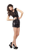 Fashion model in sequin dress. Attractive young woman posing in sequin dress. Hands on the hips, provocative look. Studio image, isolated on white background Stock Image