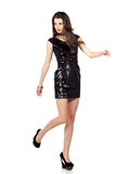 Fashion model in sequin dress. Attractive young woman posing in sequin dress, walking. Studio image,  on white background Royalty Free Stock Photos