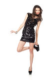 Fashion model in sequin dress. Attractive young woman posing in sequin dress, with alluring smile and looking at camera, playing with shoes. Studio image,  on Stock Image