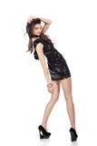 Fashion model in sequin dress. Attractive young woman posing in sequin dress, smiling, looking at camera. Studio image,  on white background Stock Photos