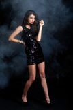 Fashion model in sequin dress. Sexy young woman posing in sequin dress, covered in fog, looking away. Studio image, on black background Royalty Free Stock Photos