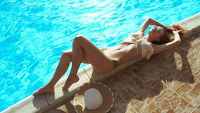 Fashion model in sexy swimsuit lying and sunbathing stock video