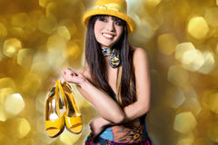 Fashion model with the shoes. Young woman is posing while shopping, wearing a yellow hat and buying the matching shoes Stock Images