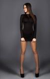 Fashion model in short black dress looking away in studio Stock Image