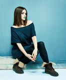 Fashion model sitting. Beautiful girl in black dre Royalty Free Stock Photos