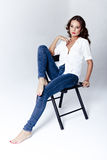 Fashion model sitting on a chair in a blouse and jeans barefoot Stock Photography
