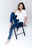 Fashion model sitting on a chair in a blouse and jeans barefoot Royalty Free Stock Photography