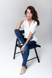 Fashion model sitting on a chair in a blouse and jeans barefoot Stock Photos