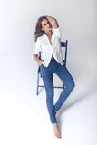Fashion model sitting on a chair in a blouse and jeans barefoot Royalty Free Stock Image