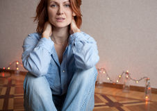 Fashion model sitting on floor in a blouse and jeans Royalty Free Stock Photos