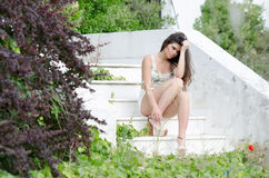 Fashion model , sitting on stairs covered by wild green bush Stock Images