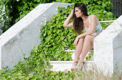 Fashion model, sitting on stairs covered by wild green bush Stock Images