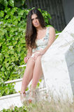 Fashion model , sitting on stairs covered by wild green bush Royalty Free Stock Photos