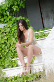 Fashion model , sitting on stairs covered by wild green bush Royalty Free Stock Photo
