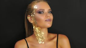 Fashion model standing against the black wall and striking a pose for studio fashion photo shoot. stylish golden makeup. Fashion model standing against the black stock footage