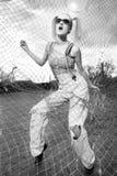 Fashion model standing behind net webbing Stock Image