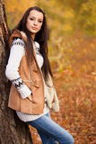 Fashion model standing near tree in autmn park Stock Image
