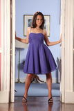 Fashion model strikes pose in doorway. Beautiful young fashion model wearing blue cocktail dress, strikes pose in the doorway of hotel lobby royalty free stock image