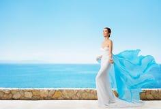 Fashion Model in Summer Dress, Elegant Woman in Long White Gown. Fashion Model in Summer Dress Over Blue Sea, Elegant Woman in Long White Gown over sky stock image