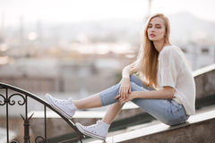 Fashion model. Summer look. Jeans, sneakers, sweater. On city background Royalty Free Stock Photo